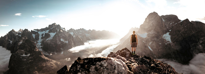 a mountain climber standing on top of a summit in greenland