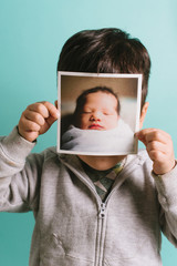 Little kid holding up baby picture