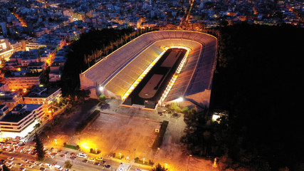 Aerial drone night shot of illuminated beautiful ancient stadium of Kalimarmaro or Panathenaic where first classic Olympic games were held at dusk with beautiful colours, Athens, Attica, Greece