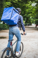 Rear view of food delivery man riding bicycle on street in city