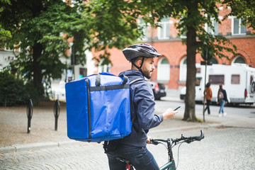 Food delivery man with bicycle looking away while standing on street in city