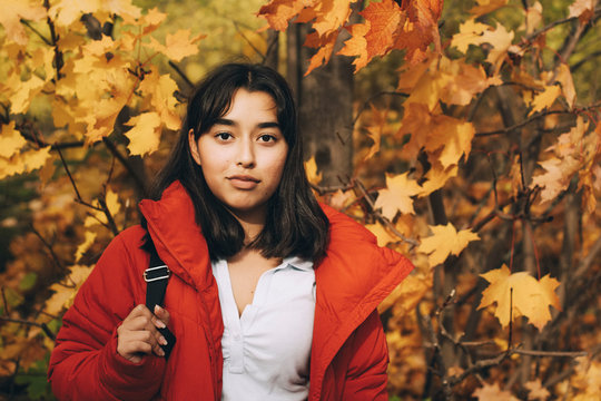 Portrait of girl in red jacket standing against maple trees