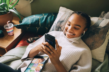 High angle view of smiling teenage girl listening music while using mobile phone on bed at home