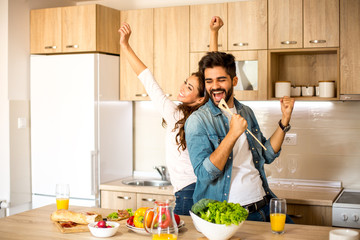 Two attractive Caucasian male and female friends enjoying in cooking, dancing and singing in the kitchen. Fotobehang