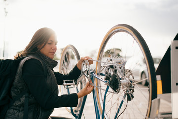 Side view of businesswoman repairing bicycle chain on footpath in city