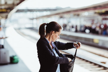 Mature businesswoman searching in bag at train station