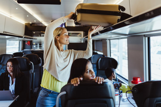 Woman keeping luggage on shelf while traveling with children in train