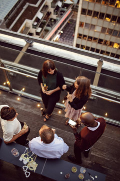 High angle view of business colleagues talking while enjoying office party on terrace
