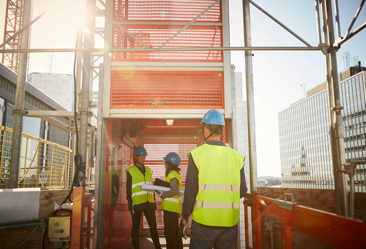Male and female engineers at freight elevator in construction site