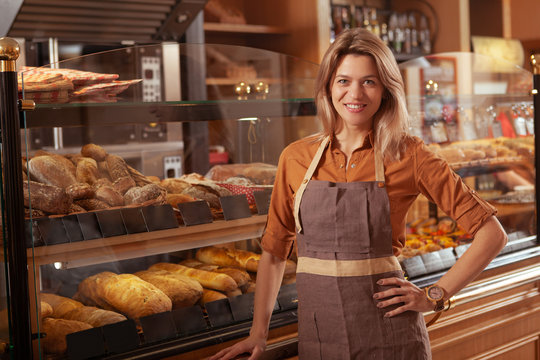 Charming mature female baker enjoying working at her bakery store, copy space