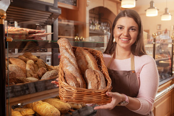 Proud female baker holding basket of delicious bread, working at her bakery, copy space