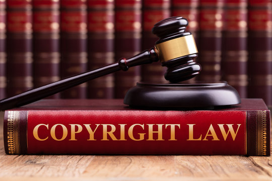 Copyright Law Book And A Judge Gavel On Desk