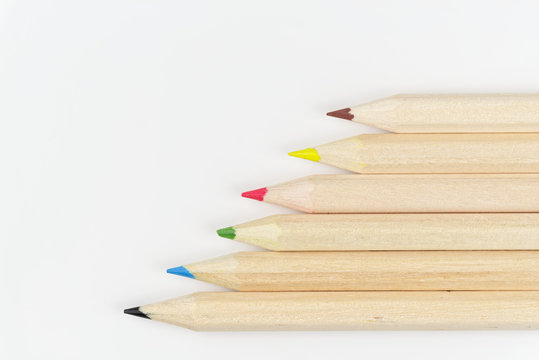 Set of colored pencils on a white background arranged in a row