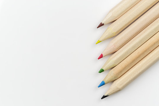 Set of colored pencils on a white background arranged in a raw