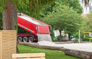 Ein LKW kippt neuen Sand auf einen Sportplatz