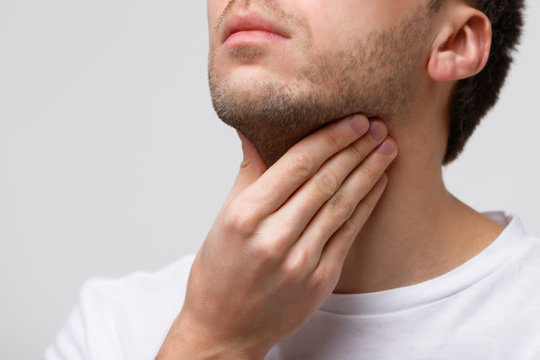 Close up of sick man suffering from throat problems, grey background, isolated. Thyroid gland, painful swallowing, pharyngitis, laryngeal swelling concept. Inflammation of the upper respiratory tract