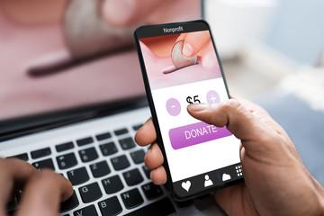 Man Donating Money On Mobile Phone