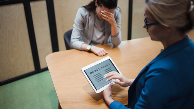 Job interview. The recruiter holds a tablet with a check list of the necessary skills of the candidate.