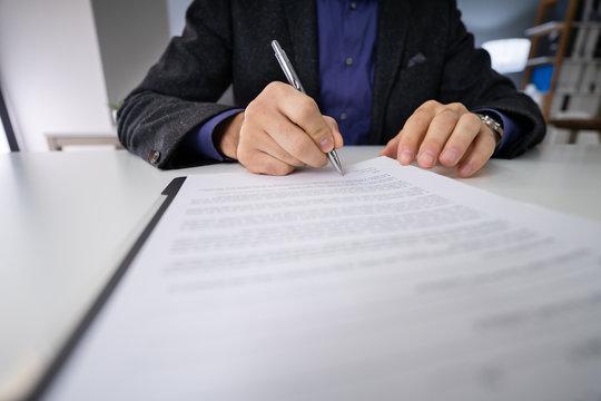 Close-up Of Businessman Holding Pen