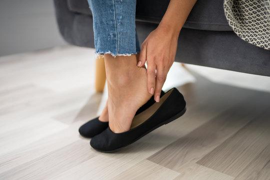 Woman's Hand Removing Uncomfortable Ballerinas