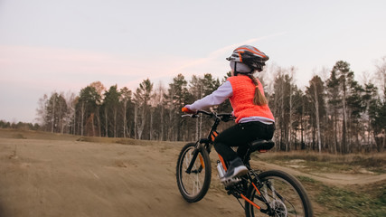 One caucasian children rides bike road track in dirt park. Girl riding black orange cycle in racetrack. Kid goes do bicycle sports. Biker motion ride with backpack and helmet. Mountain bike hardtail.