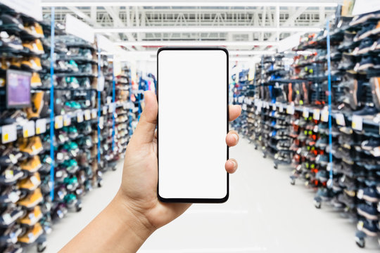 Mockup smartphone with sport shoes on shelves in sneakers shop modern sports supermarket background. Mock up mobile phone with blank screen for your advertisment.