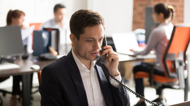 Company employee sitting in shared office talking on landline