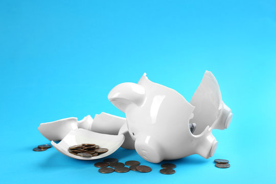 Broken piggy bank with money on blue background