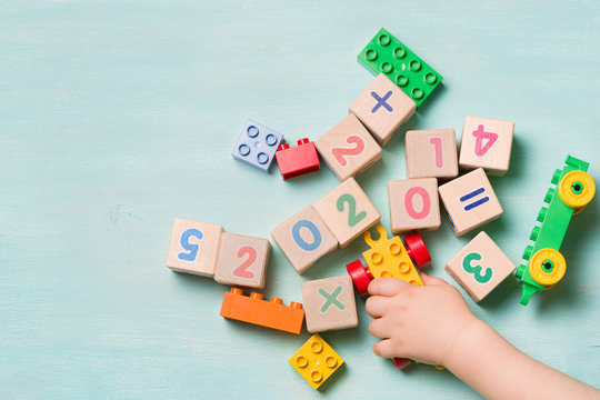 Little cute toddler boy playing with colorful cubes and bricks on a turquoise table. Top view on wooden cubes with numbers of the year 2020. Educational games for children and early development.