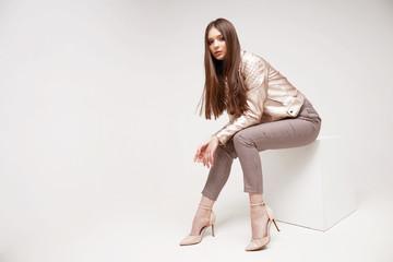 Fashion model in golden leather jacket posing in studio.