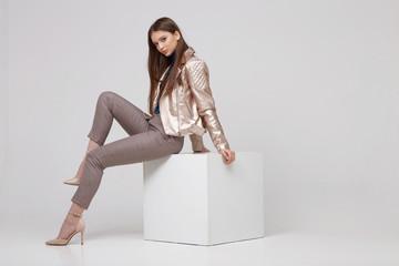 Fashion model in golden leather jacket posing in studio. Wall mural