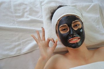 Beautiful young woman relaxing with face mask at beauty spa. Woman getting facial black mud mask at beauty salon. Wall mural