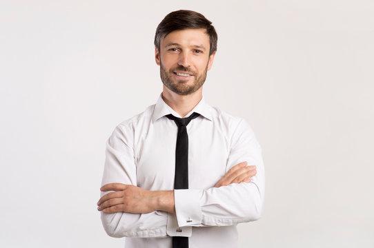 Positive Business Guy Smiling Crossing Hands Standing In Studio