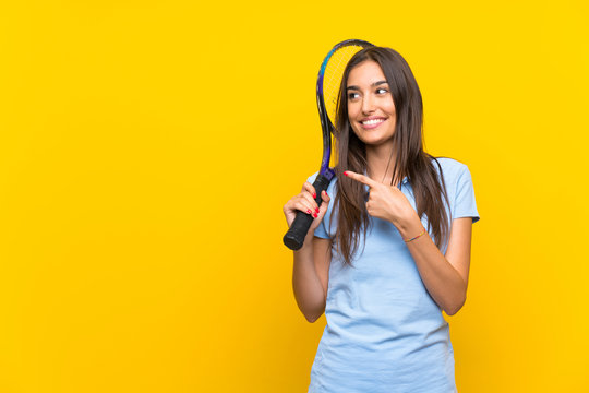 Young tennis player woman over isolated yellow wall pointing to the side to present a product