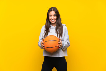 Young woman playing basketball over isolated yellow background