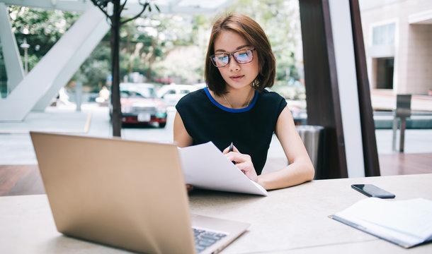 Pensive Asian freelancer in glasses reading review