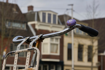 In de dag Fiets Steer of old bicycle with shiny and rusty steel tubes and purple ring in focus with blurry buildings in the background, Utrecht the Netherlands