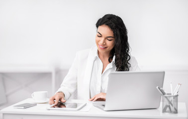 Cheerful latin girl using touchpad with smile at working place Wall mural