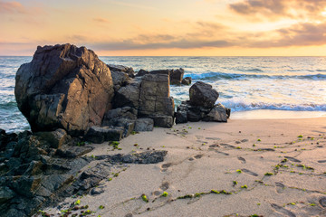 sea beach at sunrise. calm waves wash huge rocks. golden clouds on the sky. stunning marine scenery in morning light.