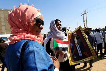 Supporters of Sudanese former president Omar Hassan al-Bashir carry his picture during a protest outside the court house that convicted him on corruption charges in Khartoum