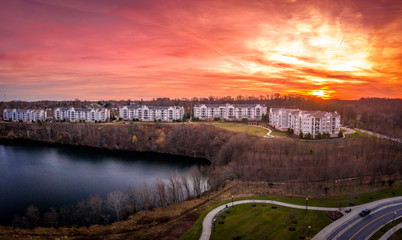 Foto auf Acrylglas Hochrote Aerial sunset view of luxury upscale residential condominium, condo and apartment complex with a lake view in Maryland USA, prime American real estate with dramatic colorful sky