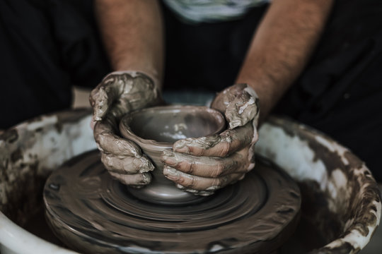 Hands of craftsman artist working on pottery wheel.Selective Focus .