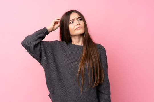 Young woman over isolated pink background having doubts while scratching head