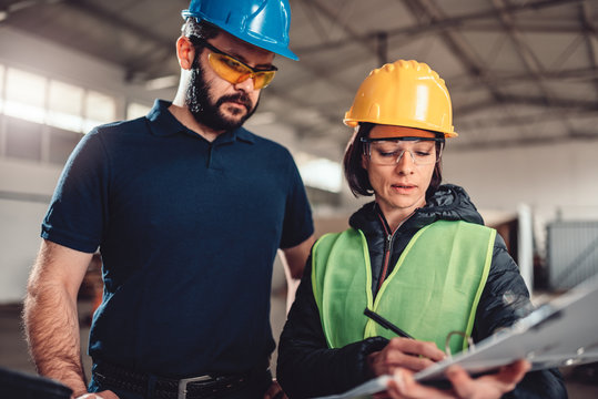 Workplace safety inspector writing a report at industrial factory