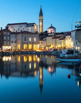 Night view of old city Piran in Slovenia. Beautiful cityscape through marina to Tartini Square.