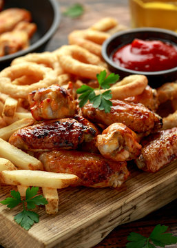 Fried Chicken wings with onion rings, french fries and dipping sauce. take away food.