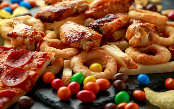 Unhealthy, Fast food concept. onion rings, pizza, french fries, bbq chicken, candy, chocolate, potato chips, salt peanuts.