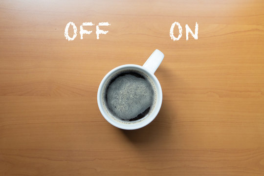 Coffee break. Cup of coffee on desk, switched on,Cup of coffee on wooden table, top view