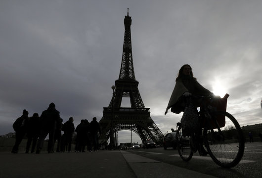A woman rides a bicycle near the Eiffel tower as a strike by all unions of the Paris transport network (RATP) and French SNCF workers entered its tenth consecutive day in Pari