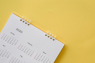 close up top view on white calendar 2020 month schedule to make appointment meeting or manage timetable each day lay on yellow background for planning work and life concept